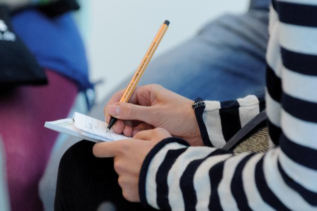 Mensch mit Stift macht Notizen